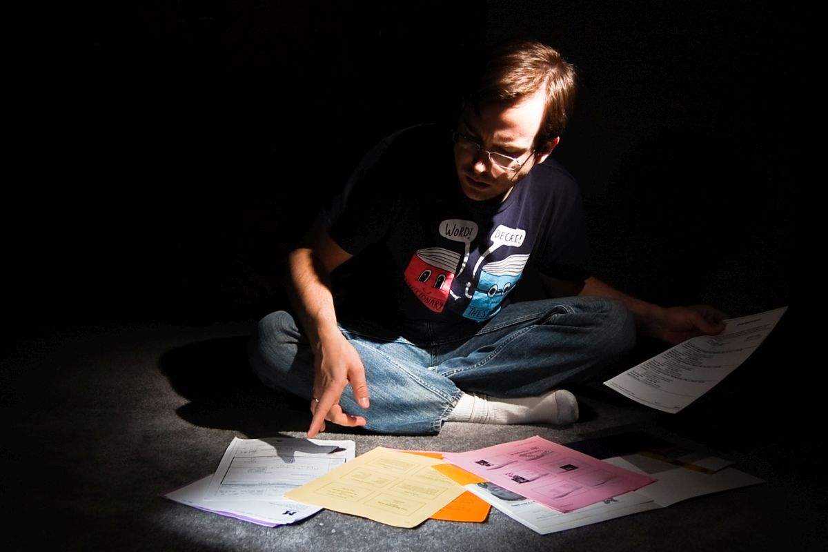 Man in the dark with paperwork